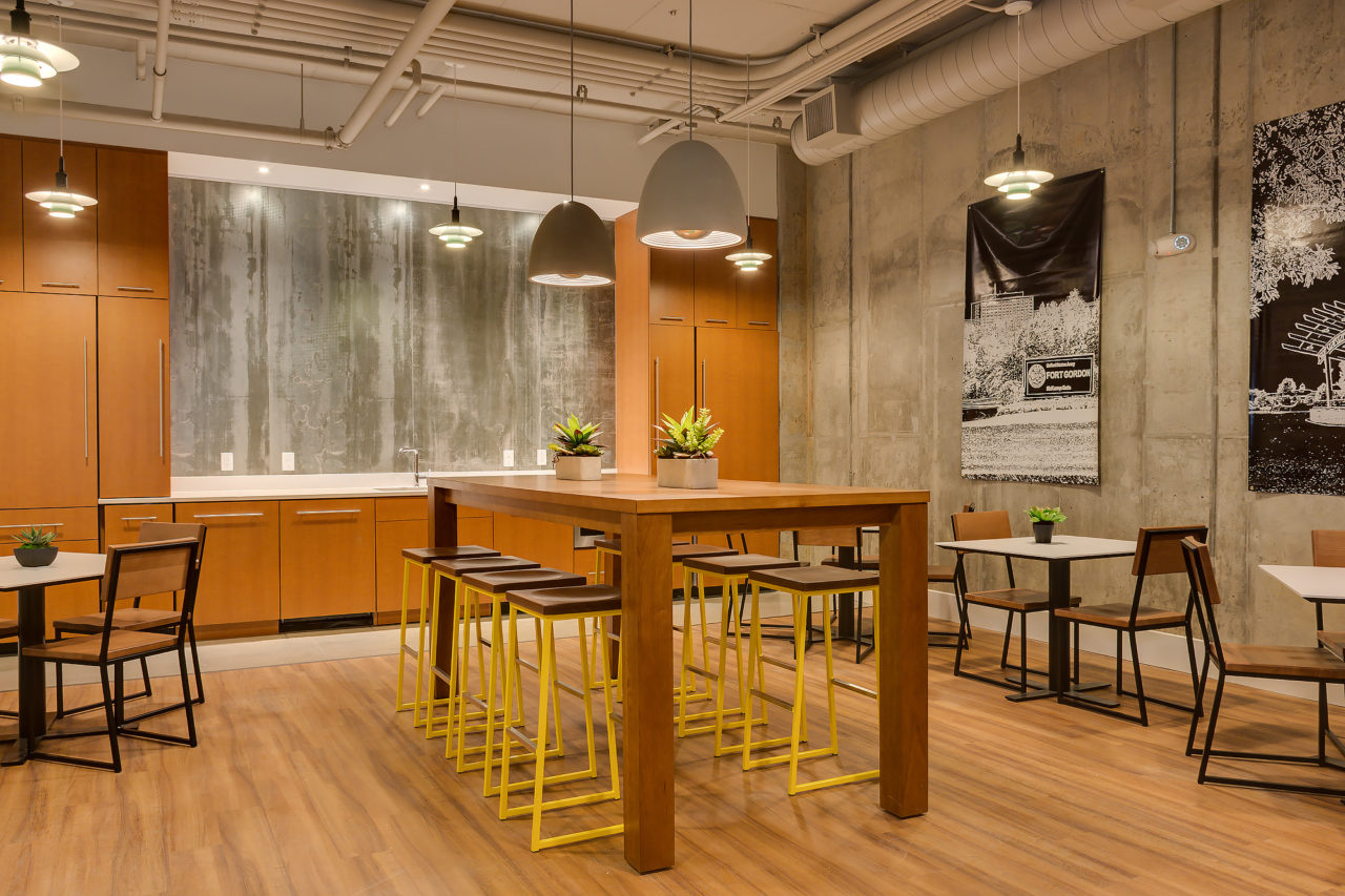 A warm and spacious office cafeteria with industrial chairs and barstools.