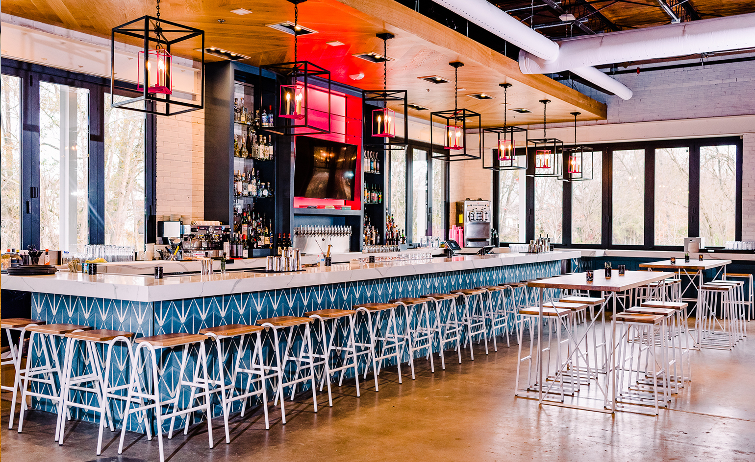 Modern barstools lined up against graphic cement tiles in a Mexican themed restaurant