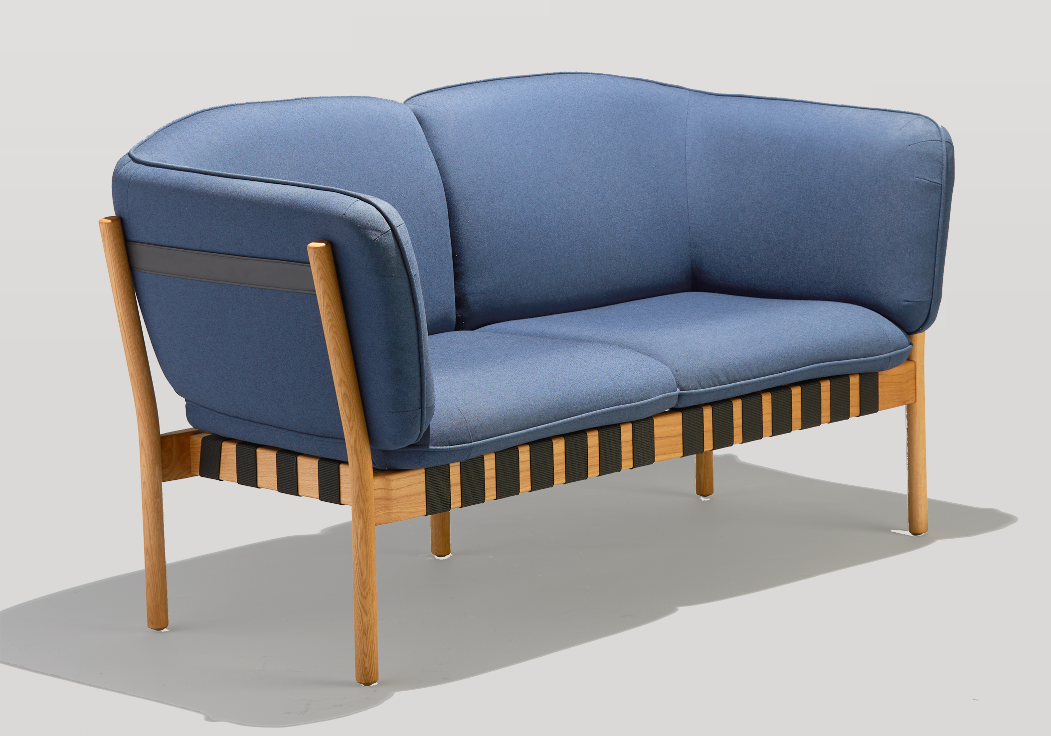 Dowel Love Seat with blue upholstery, white oak legs, and black top strap