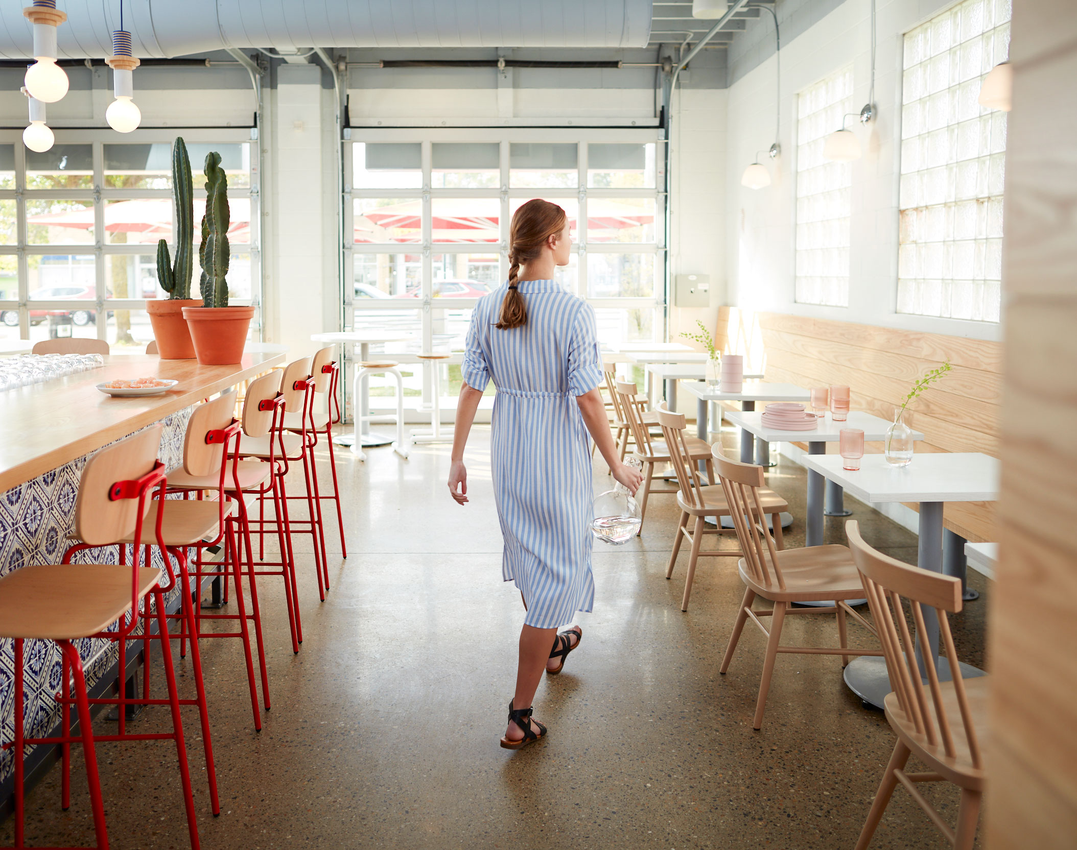 Reece barstools and Hugh chairs fill the inside of a modern, sunny diner.