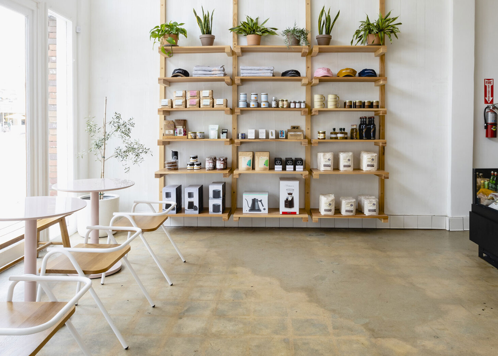 Bakery interior with white walls, wooden shelving, and minimal modern restaurant chairs.