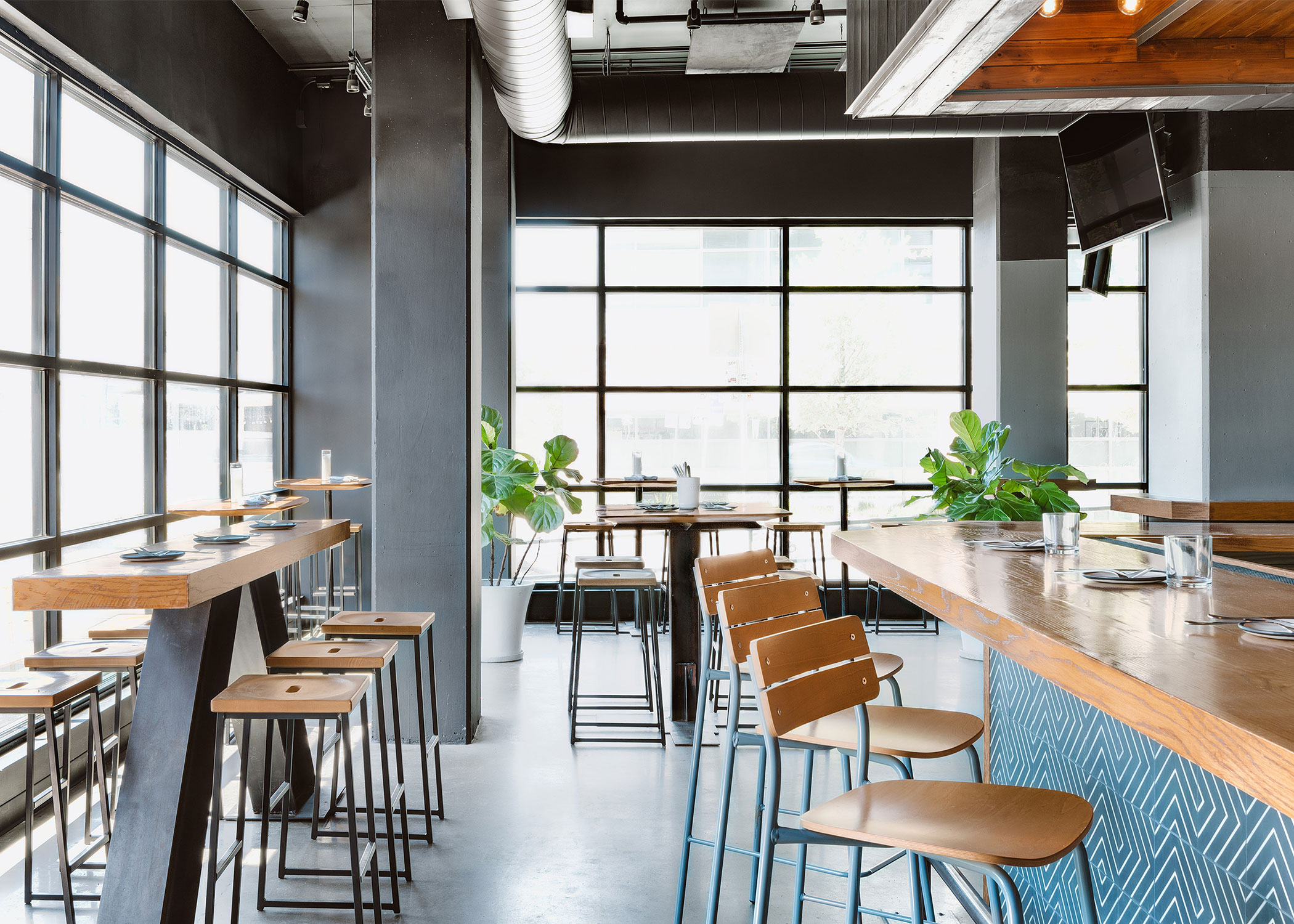 Honey finished wood and dusty steel powder coated steel barstools in a bright windowed interior.