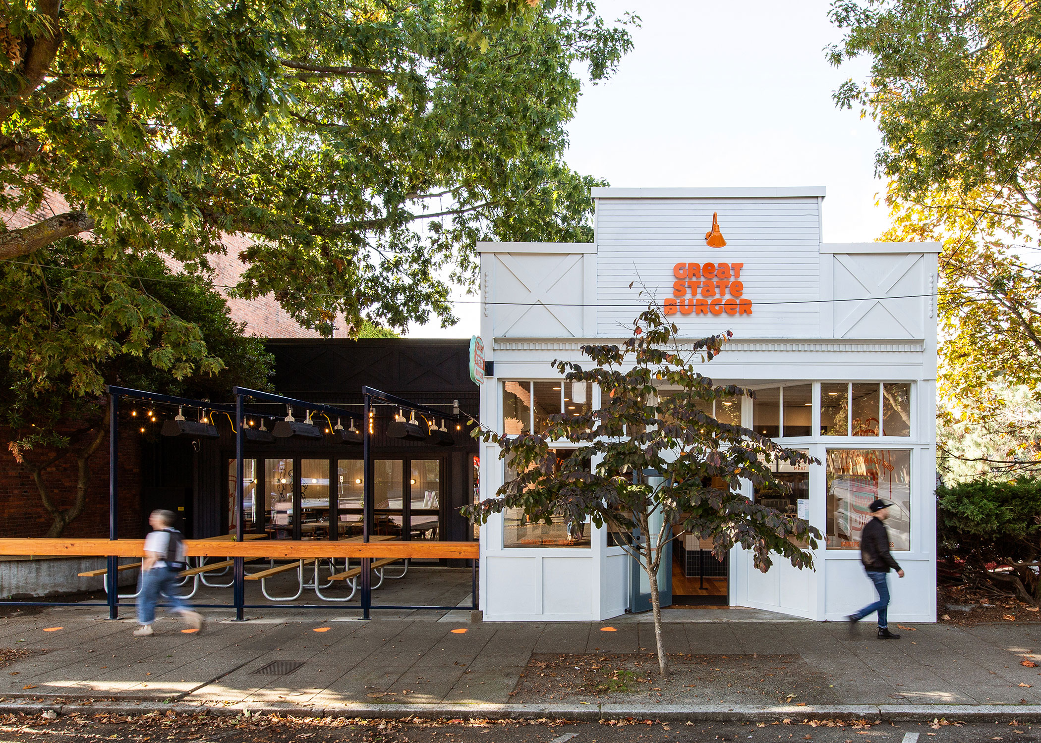 Exterior shot of the modern, colorful burger restaurant, Great State Burger. Orange signage and outdoor seating