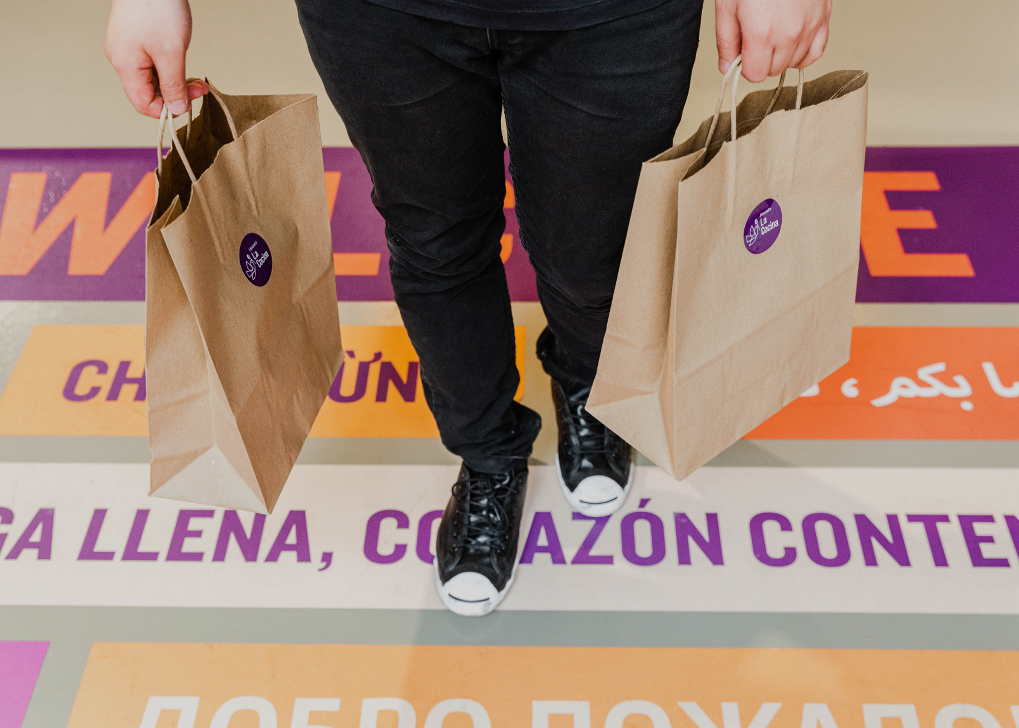 A person in black pants walking across the floor with take-out food bags.